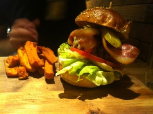 Steak burger with streaky bacon and cheddar cheese and sweet potato fries