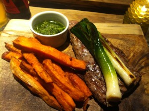 Steak with chimichurri sauce, sweet potato fries and grilled baby leeks
